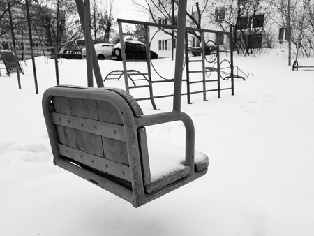Childrens playground near the house in the winter in the snow - swing Фото со стока