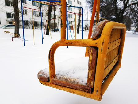 Children playground near the house in the winter in the snow - swing