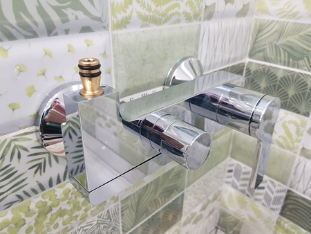 Riparazione e impianto idraulico - rubinetto dell'acqua su una piastrella in bagno