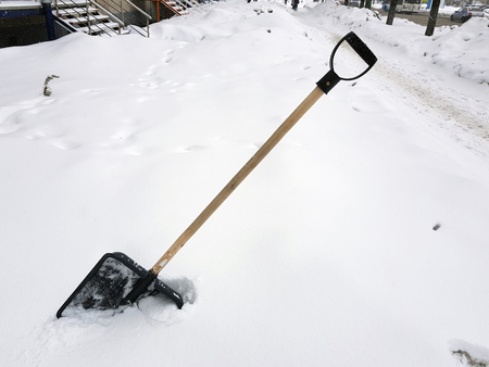 Beautiful snow shovel and ice ax stuck in the snow in winter