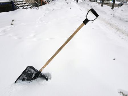 Schöne Schneeschaufel und Eispickel stecken im Winter im Schnee