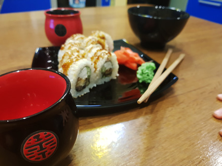 Very beautiful appetizing rolls on a black plate with soy sauce and chopsticks Imagens