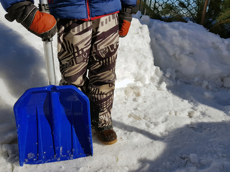 Snow shovel in the hands - a beautiful child cleans snow in the winter or spring in sunny weather