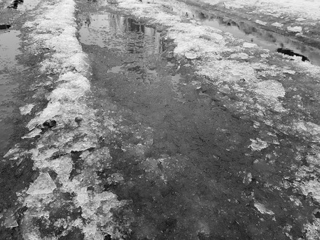 Very beautiful puddles with a crust of ice, snow and reflection in the winter or spring