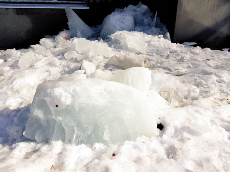A dangerous large ice block fell from a roof in winter or spring Stock Photo