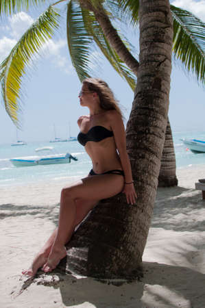 Beautiful girl posing for a photo sitting on a sandy beach on the Caribbean coast. On a Sunny day with yachts in the background