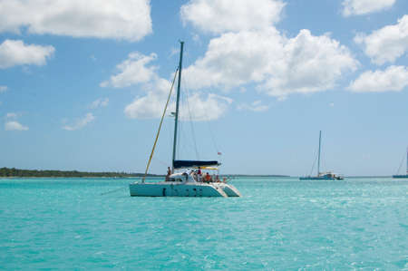 Sailing yachts and catamarans with motor boats in the Caribbean sea off the island of Saona