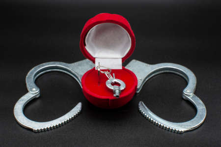 Forbidden love behind bars. Wedding between prisoners in prison. Clipart with open handcuffs, in the form of a heart. The keys to the handcuffs in the wedding ring box, adultery, infidelity of the husband and wife.