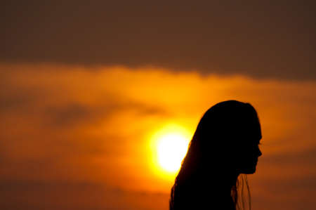 Silhouette of a dancing girl at sunset in the rays of the Golden sun. On the beach of the Arabian sea Indian ocean in India GOA