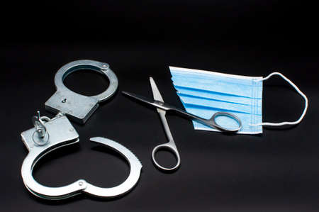 Medical mask that will not protect against coronavirus and pandemics cut with scissors, like the keys to freedom opening handcuffs and the path to freedom
