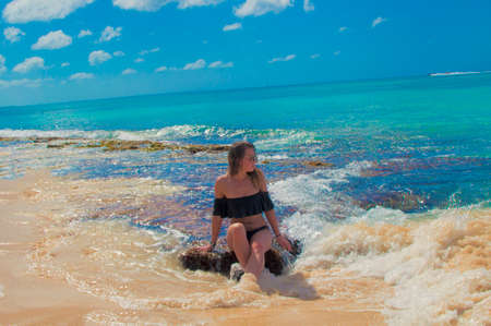 Stylized color filters image of a girl on a beautiful beach in summer against the background of a beautiful sea