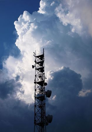 antenna cellular operator with the radiating transmitter in the background of thunderclouds