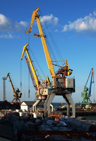 docker: marine cranes in the port closeup to the background of blue sky with clouds     Stock Photo
