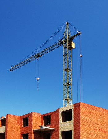 Multistory building from brick under construction with no roof and construction crane Stock Photo