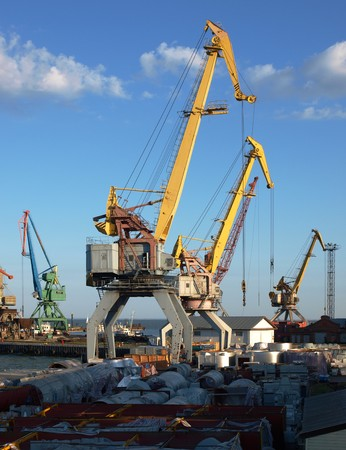 docker: marine cranes in the port closeup to the background of blue sky with clouds