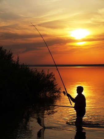 pecheur: Pêcheur attrape le poisson en faisant tourner sur le lac au coucher du soleil