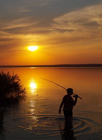 Fisherman catches fish by spinning on the lake at sunset photo