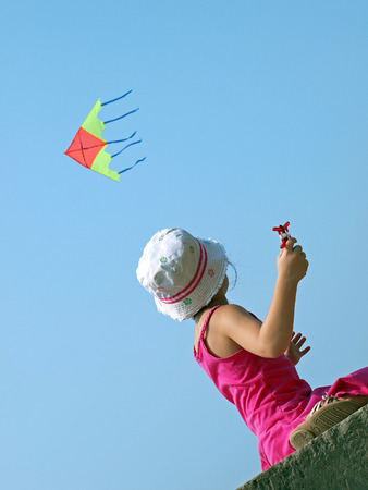 vacaton: Little child playing with a kite on a background of blue sky Stock Photo