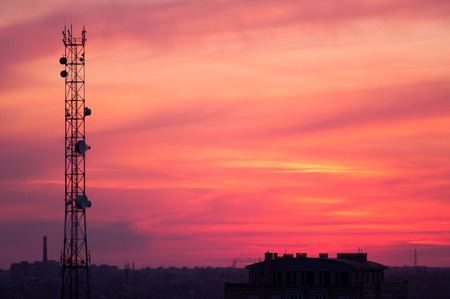 Cell tower and city buildings at sunset photo
