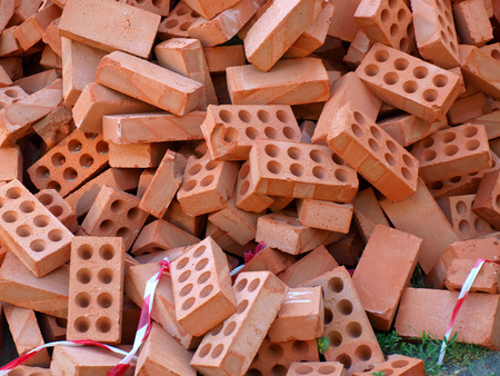 disorganization: A large pile of red bricks for the construction in a full disorder