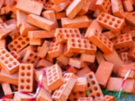 disorganization: Defocused and blur image of large pile of red bricks for the construction in a full disorder Stock Photo