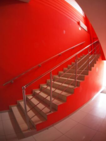 second floor: Defocused and blur image of a staircase in an office on the second floor in the hallway with red walls with blurred background with wide angle distortion view