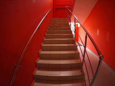 second floor: Corridor with red walls and a staircase with steps to the second floor inside the building with wide angle distortion view