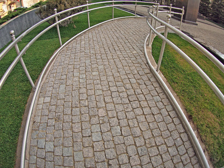 challenged: Ramp for physically challenged from the granite pavement with wide angle fisheye lens and distortion view Stock Photo