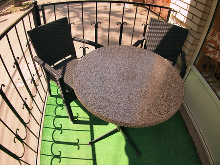 round chairs: Round empty table in marble and two chairs in a cafe on the street with wide angle distortion view
