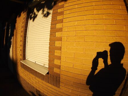 illuminated wall: The shadow of a man on the illuminated wall of a house with a camera in hand with wide angle distortion view Stock Photo