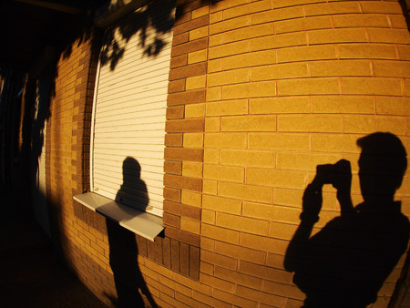 illuminated wall: The shadow of a man with a camera on the illuminated wall, who photographs people on the street