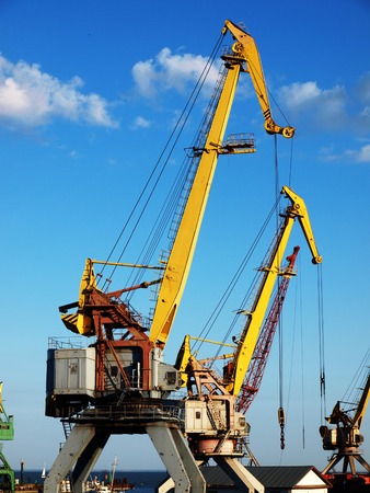 docker: marine cranes in the cargo port closeup to the background of blue sky with clouds