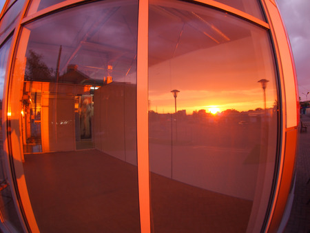 premises: Cityscape at sunset which is reflected in the window of an empty shop premises with wide angle fisheye lens and distortion view
