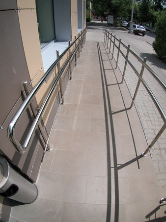 Ramp for physically challenged from the tiled pavement with wide angle fisheye lens and distortion view
