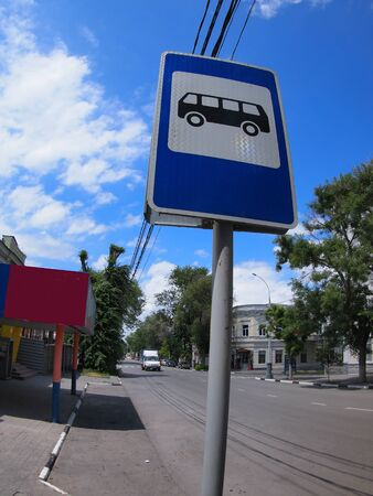 Road sign with a picture of a bus stop on a city street with wide angle distortion view