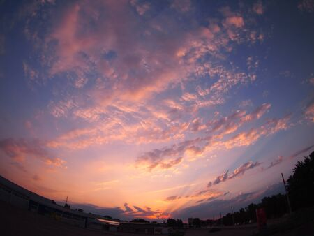 distortion: Skies and clouds over the city at sunset with wide angle distortion view