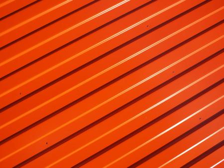 longitudinal: Orange metal corrugated sheet metal with longitudinal stripes and striped shadows illuminated bright sun to use as background