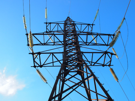 insulators: Bottom view of the high-voltage metal tower with electrical wires and insulators against the blue sky