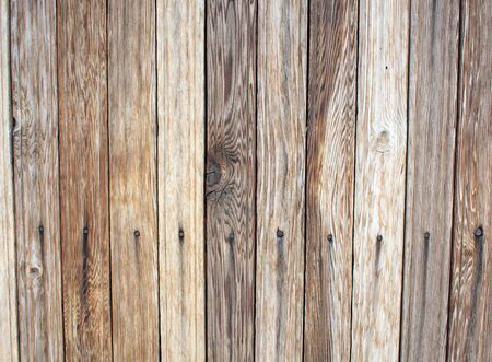 unpainted: Fragment of an old wooden wall made of unpainted boards with clearly visible texture of natural wood for use as background or wallpaper. Stock Photo