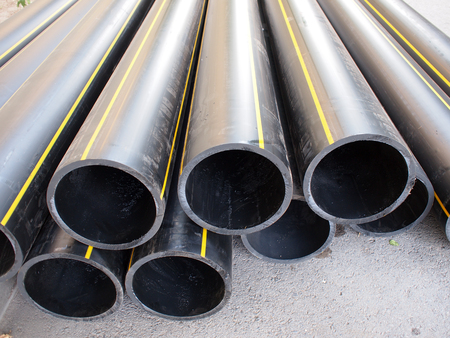 diameter: Big black pipe closeup plastic large diameter for the repair of communications are a heap on the gray pavement Stock Photo