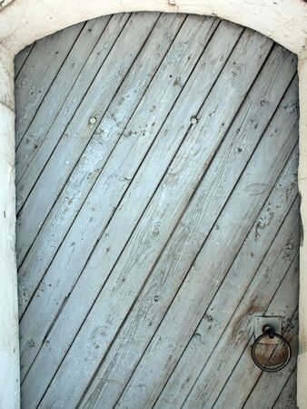 semicircular: The door of the wooden planks on the diagonal, with a semicircular top and rusty iron ring