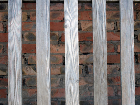 unpainted: Gray unpainted wooden planks with natural texture on the background wall of red brick