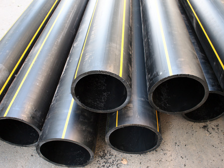 diameter: Big black pipe closeup plastic large diameter for the repair of communications are a heap on the pavement
