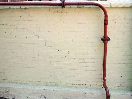 crack pipe: Wall of yellow plaster with cracks through which passes an old red gas pipe
