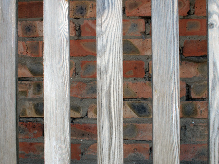 unpainted: Gray unpainted wooden planks with natural texture on the background wall of red brick. Between boards have large gaps, they are far from each other Stock Photo