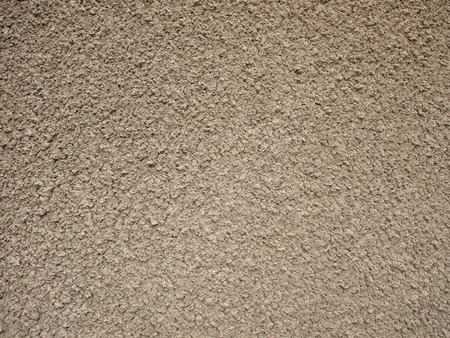 granular: Granular surface of the cement beige. It occupies the entire space of the image. It can be used for background or wallpaper