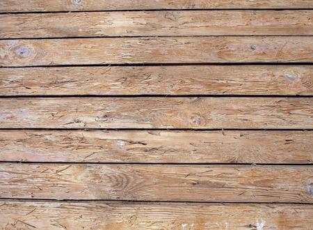 unpainted: Fragment of an old wooden fence made of unpainted boards with clearly visible texture of natural wood for use as background or wallpaper. Stock Photo
