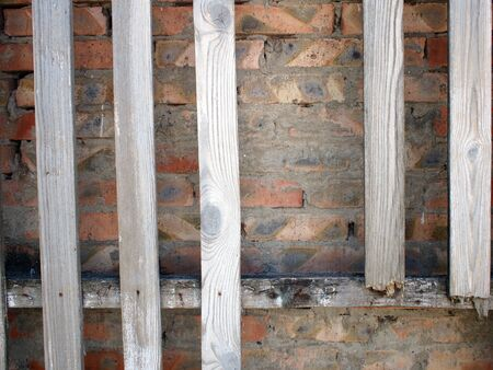 unpainted: Old wooden, unpainted and rotten boards with clearly visible structure of wood on a brick wall background Stock Photo