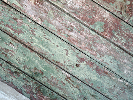 mangy: Detail of an old  diagonal wooden fence with the remains of green paint on the mangy dark boards with cracks for use as background or wallpaper