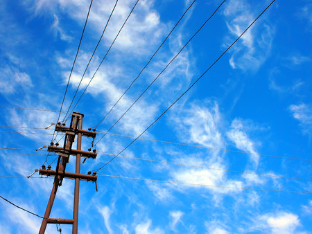 upward: Upward view on power lines and electric pole with insulators against the blue sky with clouds